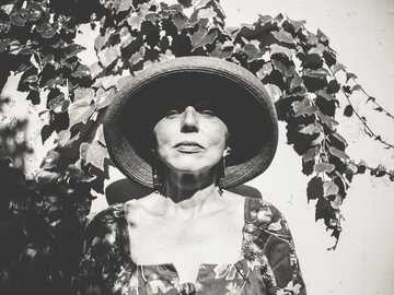 woman in hat and ivy on wall - grayscale photo of woman wearing hat.