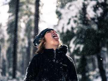 A lány kinyújtotta a nyelvét, hogy elkapja a hópelyheket. - az ember szájába ömlő hó gyorsított fényképezése. Apache-Sitgreaves Nemzeti Erdő, Arizona,