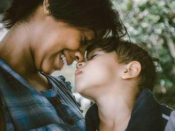 Žena a dítě dotýká tváře - selektivní zaměření fotografie ženy a chlapce. Juiz de Fora, Brazílie