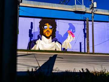 March 2020. Cleveland, OH. - white and yellow cat graffiti on blue wall. Prince Mural, Main Avenue, Cleveland, OH, USA
