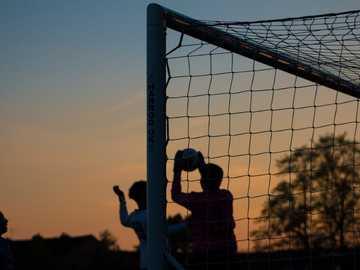 gruppo di uomini che giocano a calcio - Portiere di sagoma che cattura la palla. Ewen Fields, Hyde, Regno Unito