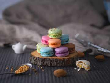 Macarons - amaretti di colori assortiti su lastra di legno.