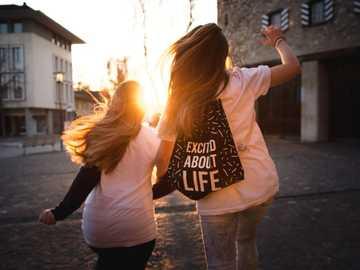 Nadšený životem - dvě ženy kráčející přes silnici při západu slunce. Brugg, Švýcarsko