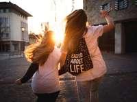 Podekscytowany życiem - dwie kobiety idące przez ulicę podczas zachodu słońca. Brugg, Szwajcaria