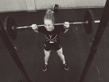 Personal training - Dunnebells - girl in red shirt and white panty holding red barbell.