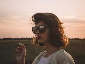 Már majdnem sötét van - szelektív összpontosít fényképezés cigaretta tartó nő. Vajdaság, Szerbia