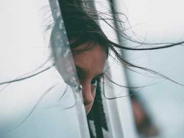 Niño asomándose por la ventana - chica asomando la cabeza en el coche de la ventana. Punto de Cinque Terre, Levanto, Italia