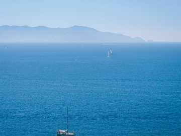 Alles blau - weißes Boot auf See während des Tages. Toskana, Italien