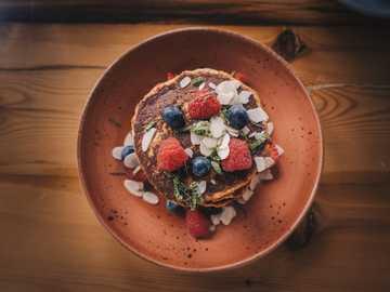 Pancakes - shallow focus fotografia di frittella con fragole e mirtilli in cima.