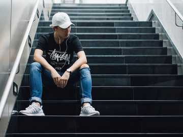 Personne assise sur les escaliers - homme assis sur un escalier noir tout en écoutant. Fullerton Bay Hotel, Singapour