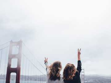Peace sign by Golden Gate Bridge - two women making peace sign near the Golden Gate bridge. San Francisco, United States