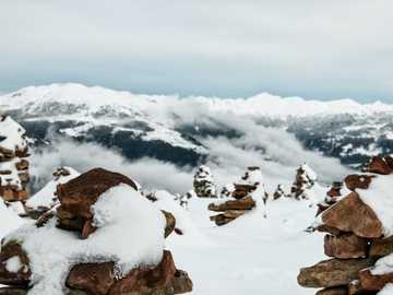 """snow-covered cairns overlooking mountains - In winter, when thick fog covers the mountain top, the """"Stoanernen Mandln"""" (cairn) seem to be su"""