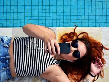 nő barna padlón feküdt - Nő iPhone-val Sao Paulóban.