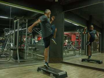 Hombre en entrenamiento de paso - hombre vestido con camisa gris y pantalón negro haciendo ejercicio.