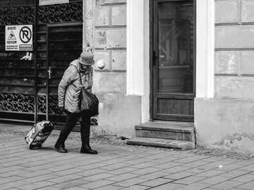 Velha Senhora - pessoa carregando bagagem, caminhando no caminho ao lado do prédio. Cluj County, Romênia