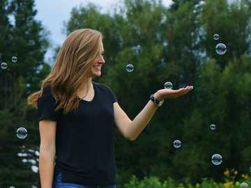woman standing in front of bubbles - Care for others and do your part, and look into yourself and see your heart. Colorado Springs, Unite