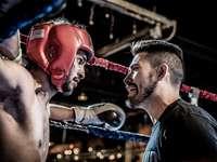 Homme en noir parlant au boxeur à l'intérieur du ring