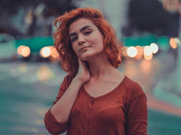 Isis Boell - woman in orange button-up cardigan selective focus photography.