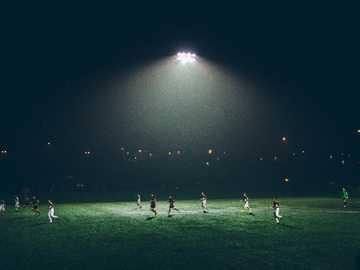 Football la nuit - groupe de personnes jouant au football sur le terrain de football.
