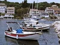 Kassiopi Hafen, Korfu, Griechenland - weißes und rotes Boot auf dem Wasser während des Tages. Kassiopi, Korfu, Griechenland