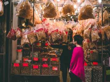 Mercato di strada di Hong Kong - fotografia di strada di donna in piedi davanti alla facciata del negozio. Hong Kong