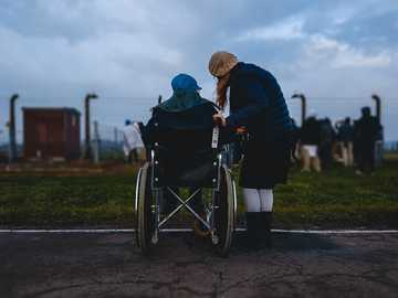 woman standing near person in wheelchair near green grass field - This is Siggy Weiser. He is a Holocaust survivor. 75 years later he is in looking as Jewish kids pra