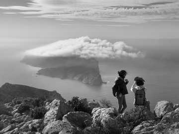 grayscale photo of two women on rock beside sea - The beauty of the Mediterranean Sea is endless. Unnamed Road, 07159 Andratx, Illes Balears, Spain, A