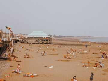 Vintage British seaside beach scene with pier - people on brown sand near body of water during daytime.