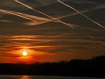 body of water during golden hour - Vienna airport air trafic over the confluence of the Morava and Danube rivers in Devín  There are