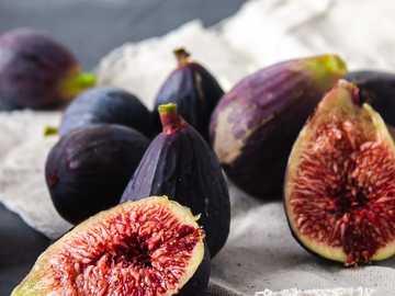 frutta rotonda viola e rossa - Fichi neri interi e mezzo tagliati su tela bianca e ardesia.