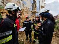 Gruppe von Menschen mit weißem Helm - Männlicher Bauingenieur leitet Katastrophenhilfetraining in Erdbebenruinen.