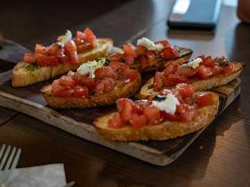 bruschetta - brown bread with tomato and green vegetable on brown wooden table. Valkenburg, Nederland