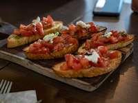 Brusqueta - pão integral com tomate e vegetais verdes na mesa de madeira marrom. Valkenburg, Holanda