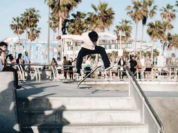 Venice street - man doing skateboard trick. Venice, Los Angeles, United States