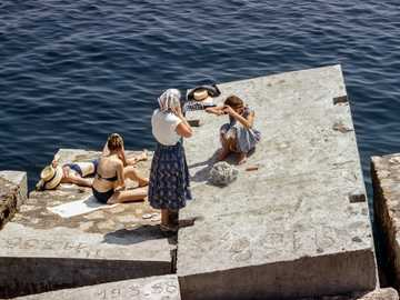Women sunbathing by the sea - Women in swimsuits and vintage clothing sunbathing on cement cubes by the sea.