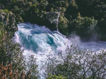river in forest at daytime - Stumbled across this tourist attraction while on a solo photography road trip. Huka Falls, New Zeala
