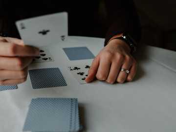 Kartenspielen - Person, die Spielkarten auf weißem Tisch hält.