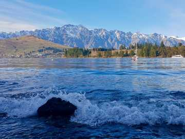 The Remarkables | Queenstown, New Zealand - green trees near body of water during daytime.