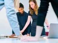 vrouw in zwart shirt met vrouw in witte broek - Vrouwelijke elektrotechnisch ingenieur ontwerpt lichtshows met team.