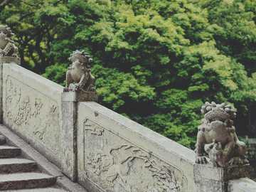 statua di cemento grigio vicino agli alberi verdi durante il giorno - Il monte Putuo si trova a est della città di Zhoushan. La città di Zhoushan è situata sull'i