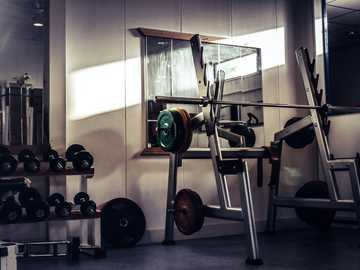barbell on rack - Old school gym lighted by a little sun stroke .