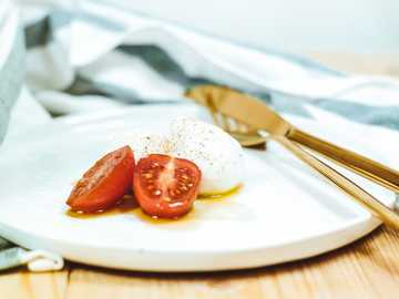 Clean food photography - sliced tomato and mozzarella cheese on white plate beside brass-colored knife and fork. Mainz, Germa