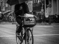 Rowerzysta w deszczu - fotografia w skali szarości przedstawiająca osobę jadącą na rowerze z parasolem. Vijzelstraat,