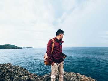 Man vid kusten - man som bär röd jacka med dragkedja som står på toppen av en stenig klippa bredvid vattenkroppen