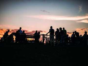 silueta de personas de pie en el balcón - Poznan, Polonia Ver cómo el sol se desvanece en el cielo durante una cálida noche de verano. Pozn