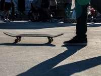 persoon die zich voor skateboard bevindt - Skateboard en schoen met sterke schaduw. Hammerpark, Lenzburg, Zwitserland