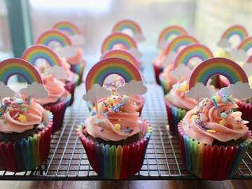 cupcake rosa e verde sulla cremagliera di metallo bianco - cupcakes, cottura al forno, arcobaleno, celebrazione, coriandoli, festa.