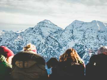 Unternberg - čtyři lidé prohlížející si během dne zasněženou horu. Unternberg, Ruhpolding, Německo
