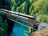 Jadący pociag w górach mostem - M......................