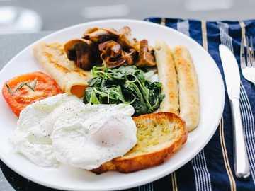 Tabelle mit Lebensmitteln und Besteck - sonniges Ei mit der Seite nach oben auf einer weißen Keramikplatte neben einem Buttermesser und ein